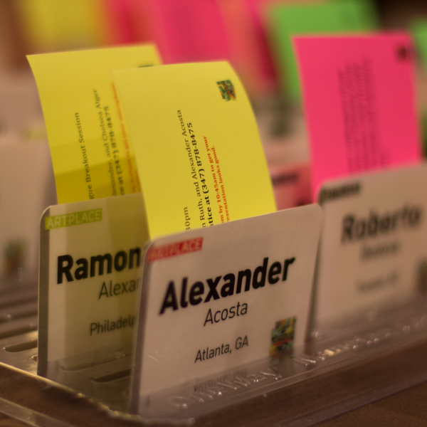 Several name tags with bright sticky papers coming out of the top