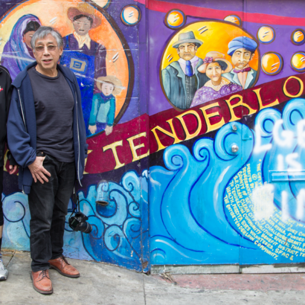 "Hanmin Liu and Jennifer Mei standing by a mural that says ""Tenderloin"""
