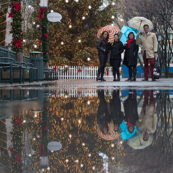 Three woman and one man under a set of umbrellas, posing by a christmas tree