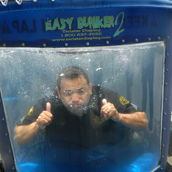 A police officer in a water tank giving a thumbs up
