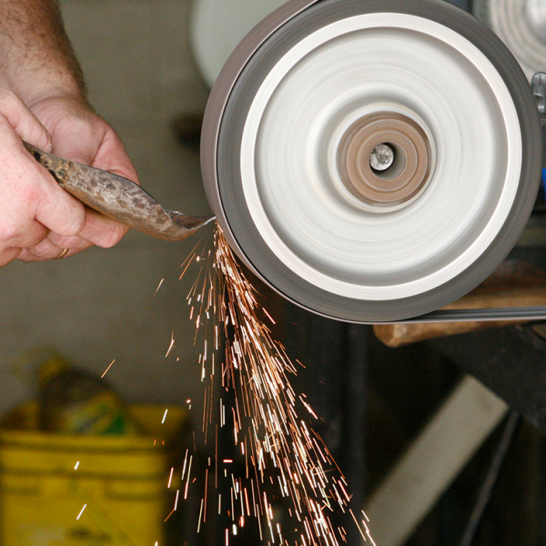 Image of a tool being sharpened and sparks flying