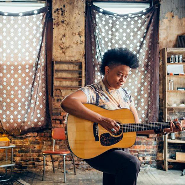 A young black woman playing the guitar.