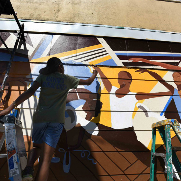 Image of an artists painting a wall mural.