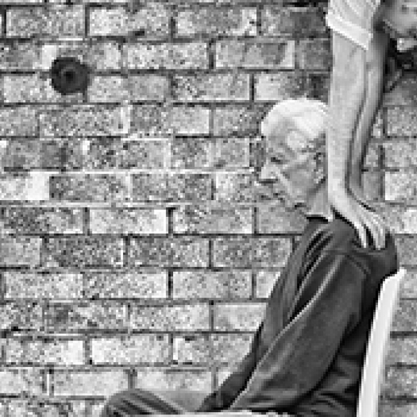Gray haired man sitting on a chair while a dancer hovers above him.