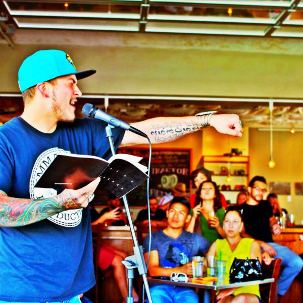 Carlos Contreras by microphone reading spoken word poetry.