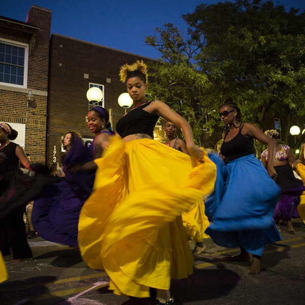 A group of dancers in bright yellow and blue skirts