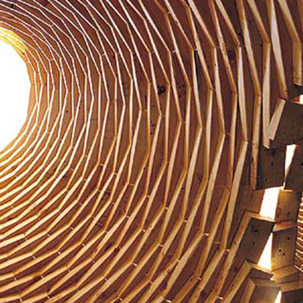 A series of wooden planks create a dome with an opening for light at the top