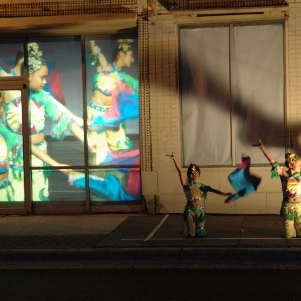 Evening, two dancers on a street with more dancers projected behind them.