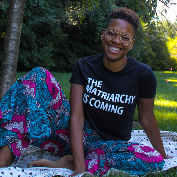 "A young Black woman sitting on the grass wearing a shirt that says ""The matriarchy is coming"""