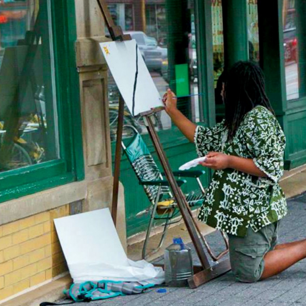 A black artists paints with an easel and canvas on an empty street