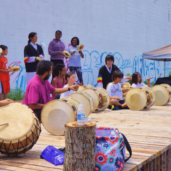 A group of people playing the drums while sitting cross-legged