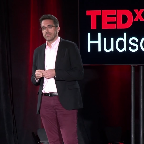 Image of Jamie Bennett on stage by a TEDx sign
