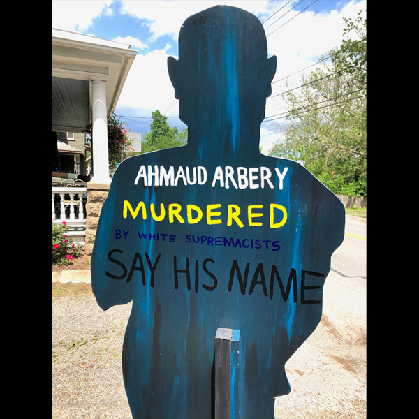 "A cardboard cut out with the words ""Ahmaud Arbery. Murdered. Say His Name."""
