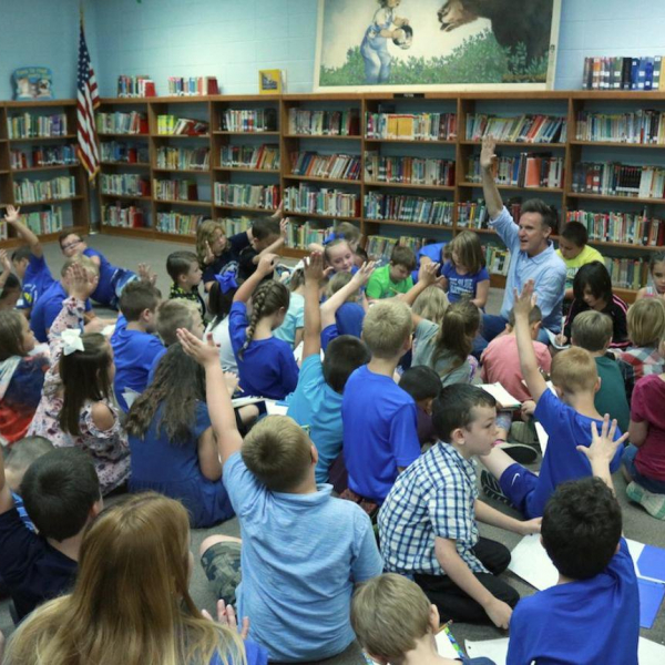 A man speaking to a group of kids in a library