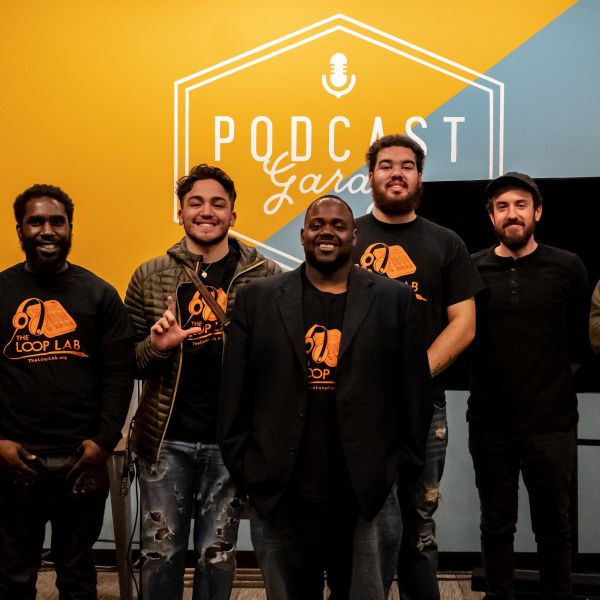 A group of young men standing in a row at a work showcase at the PRX Podcast Garage.