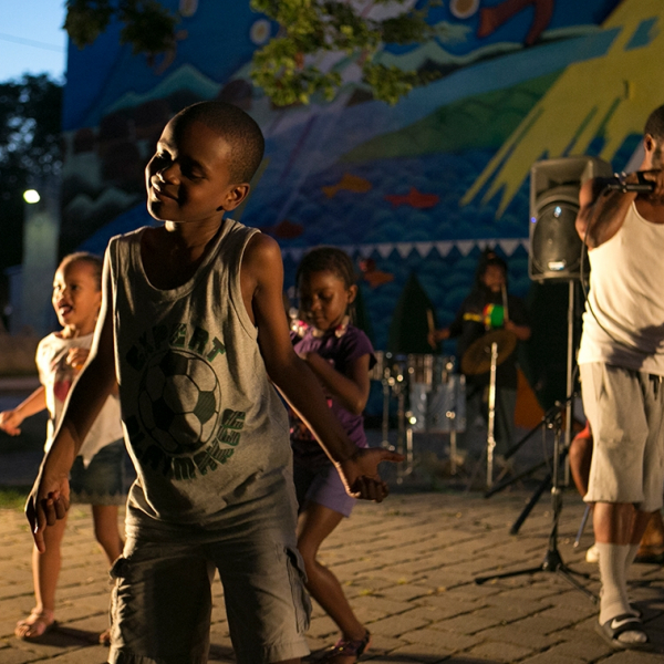 A young black boy dancing in a crowd of three.